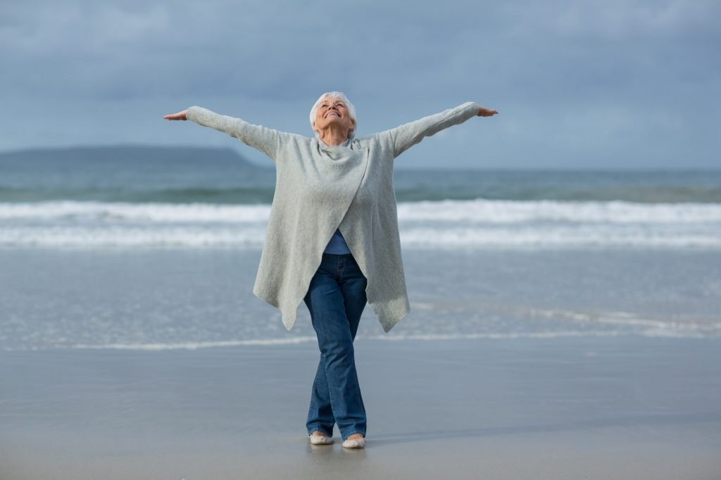 Senior woman doing stretching exercise on the beach